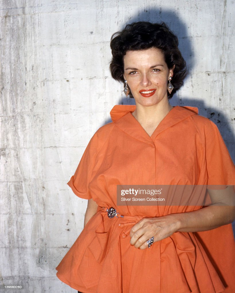 Jane Russell (1921-2011), wearing an orange dress, with large drop earrings, in a studio portrait, against a white background, circa 1955.