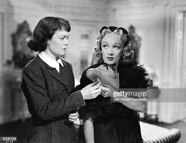 Jane Wyman and Marlene Dietrich share a cigarette in a scene from the murder mystery 'Stage Fright' directed by Alfred Hitchcock