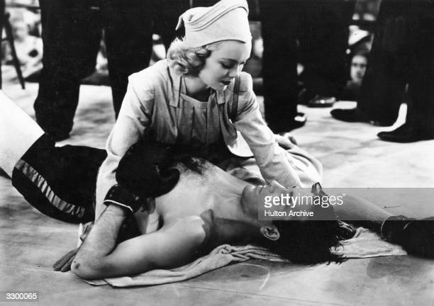 Jane Wyman the American leading lady tends to John Payne the American leading man in a scene from 'Kid Nightingale' about a boxer who sings as he...