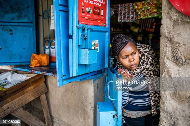 Janeffer Wacheke coowner of a freshvegetable stall waits for the arrival of a Twiga Foods Ltd's delivery truck at her stall in Nairobi Kenya on June...