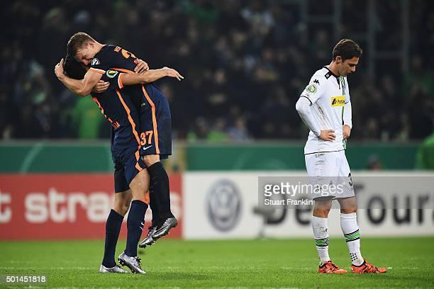 Janek Sternberg of Bremen celebrates Santiago García as Branimir Hrgota of Gladbach looks dejected at the end of the DFB Pokal match between Borussia...
