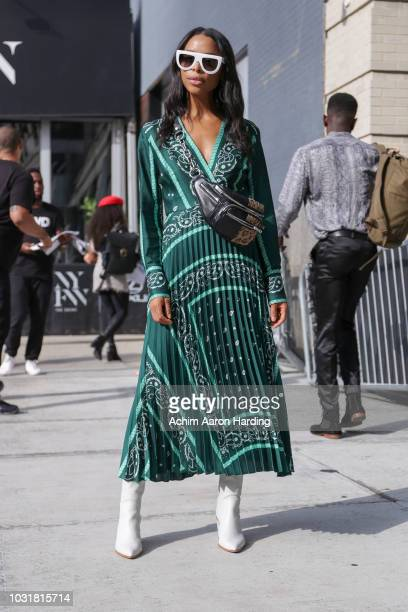 Janelle Lloyd is seen wearing a green Sandro Dress and white boots on the street during New York Fashion Week on September 11, 2018 in New York City.