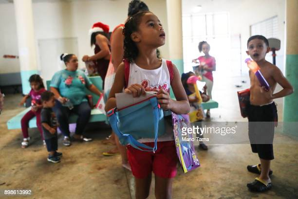 Janellise Rivera whose family lost their home in Hurricane Maria waits to receive a Christmas present from a church group in a shelter for Hurricane...