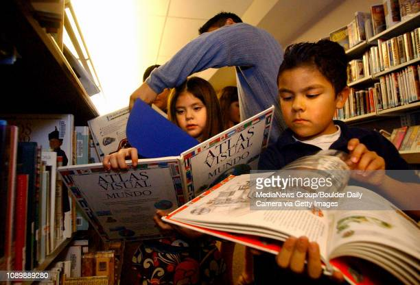 Janessa Bencomo left and her brother Mario look at books in Spanish with the help of Ricky Romero a bilingual circulation clerk at the Lafayette...