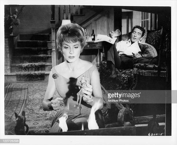 Janet Blair holding wooden sculpture while Peter Wyngarde is passed out on the couch in a scene from the film 'Burn Witch Burn' 1962