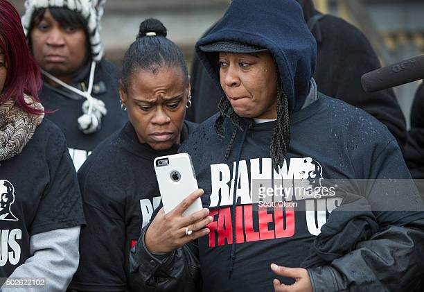 Janet Cooksey shares a picture of her son as she listens to speakers talk about the deaths of her son Quintonio LeGrier and Bettie Jones before the...