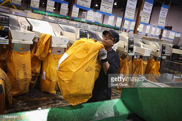 Janet Gibson loads a bag of mail onto a conveyor at the United States Postal Service Chicago Logistics and Distribution Center on December 17 2012 in...