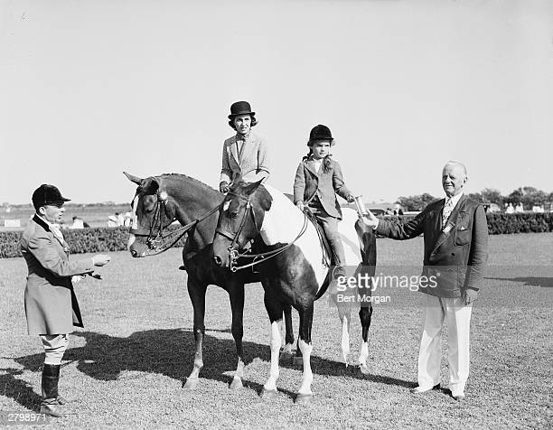Janet Lee Bouvier with her daughter Jacqueline Bouvier who accepts the 'Family Class' trophy from Albert Pardridge at the East Hampton Horse Show...