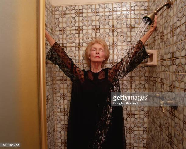 Janet Leigh, famous for her role as a murder victim in Alfred Hitchcock's Psycho, stands in a shower at home.