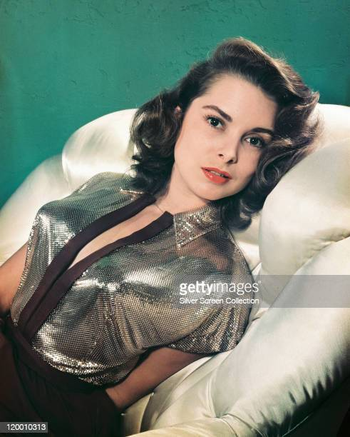 Janet Leigh US actress reclining on a white cushioned surface wearing a silver shortsleeved blouse in a studio portrait against a green background...