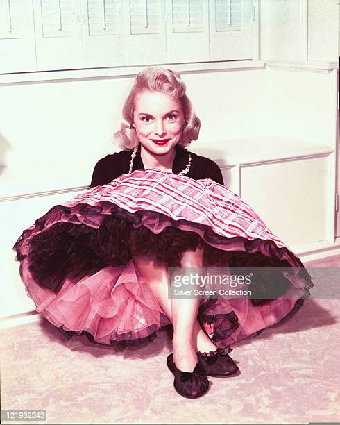 Janet Leigh US actress sitting against a white wall wearing a tartan skirt with petticoats in a studio portrait circa 1955