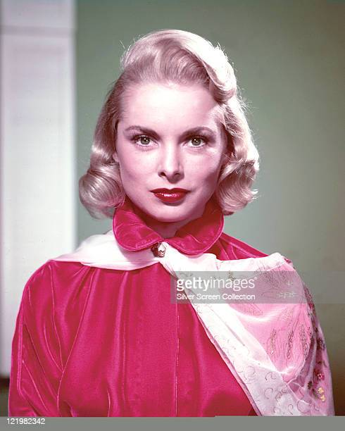 Janet Leigh US actress wearing a highneck red satin blouse with a white floral print scarf fastened at the neck in a studio portrait circa 1955