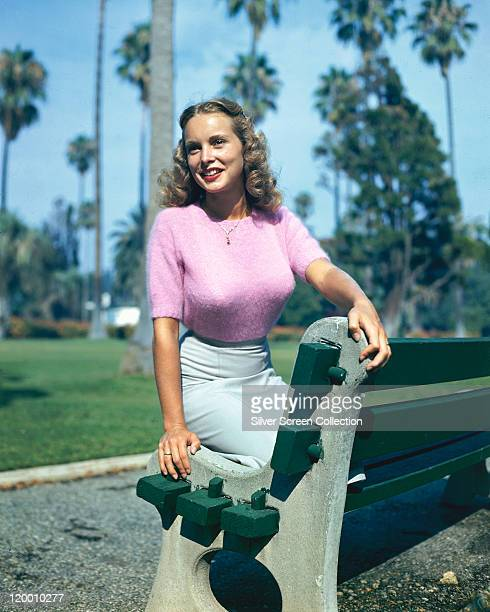 Janet Leigh US actress wearing a pink woollen jumper and a grey skirt kneeling on a park bench with trees in the background circa 1945