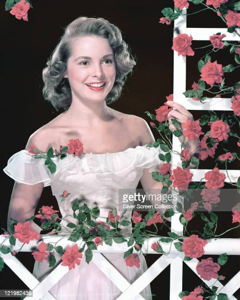 Janet Leigh , US actress, wearing a white shoulderless dress as she poses beside a white trelllis on which red flowers grow, in a studio portrait,...