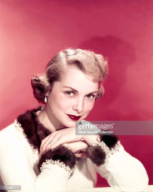 Janet Leigh US actress wearing a white woollen top with brown fur collar and cuffs in a studio portrait against a red background circa 1960