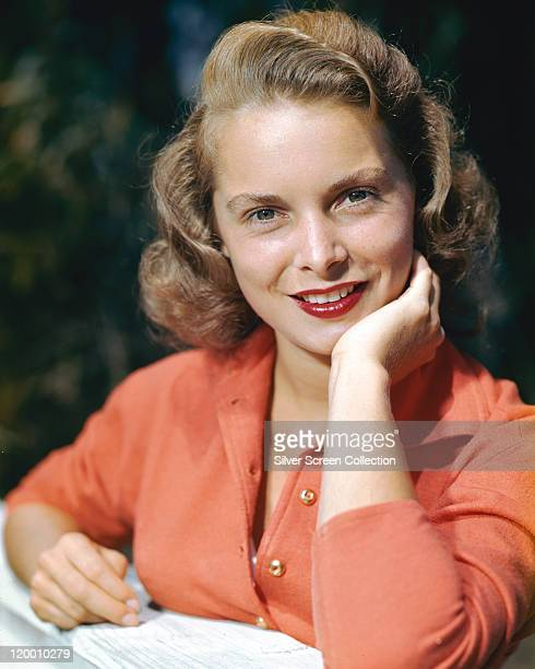 Janet Leigh , US actress, wearing an orange blouse with her chin resting on her left hand, circa 1955.