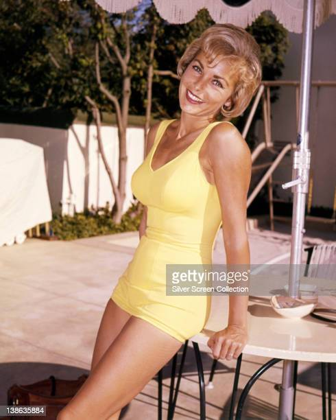 Janet Leigh wearing a yellow swimsuit as she smiles leaning against a garden table USA circa 1960