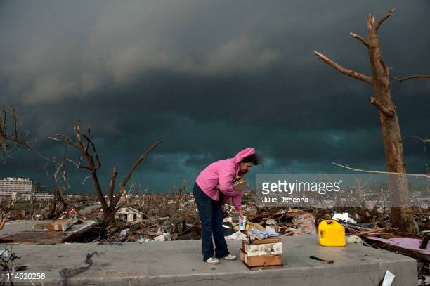 Janet Martin attempts to salvage medication and mementos from her brother's home before a second storm moves in, on May 23, 2011 in Joplin, Missouri....