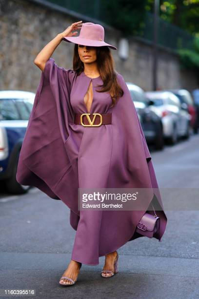 Janet Mock wears a purple hat, a purple dress, a brown large Valentino leather belt, outside Valentino, during Paris Fashion Week -Haute Couture...
