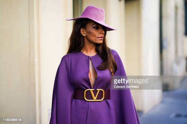 Janet Mock wears a purple hat a purple dress a brown large Valentino leather belt outside Valentino during Paris Fashion Week Haute Couture...