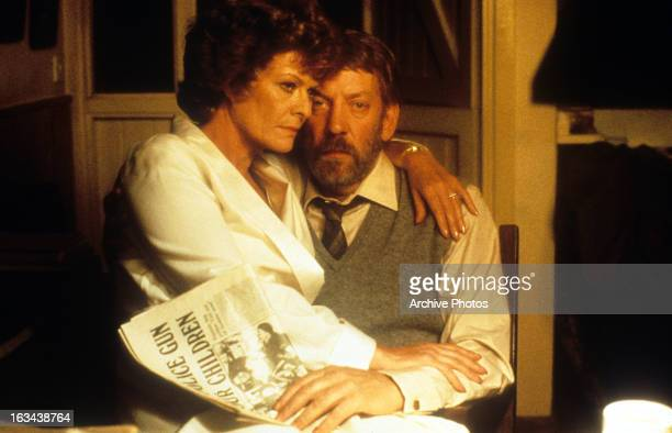 Janet Suzman sitting on the lap of Donald Sutherland in a scene from the film 'A Dry White Season' 1989