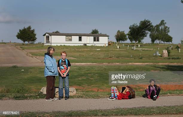 Janet Underwood waits for the school bus with her son Riley Underwood and other children in front of what used to be a trailer park before it was...