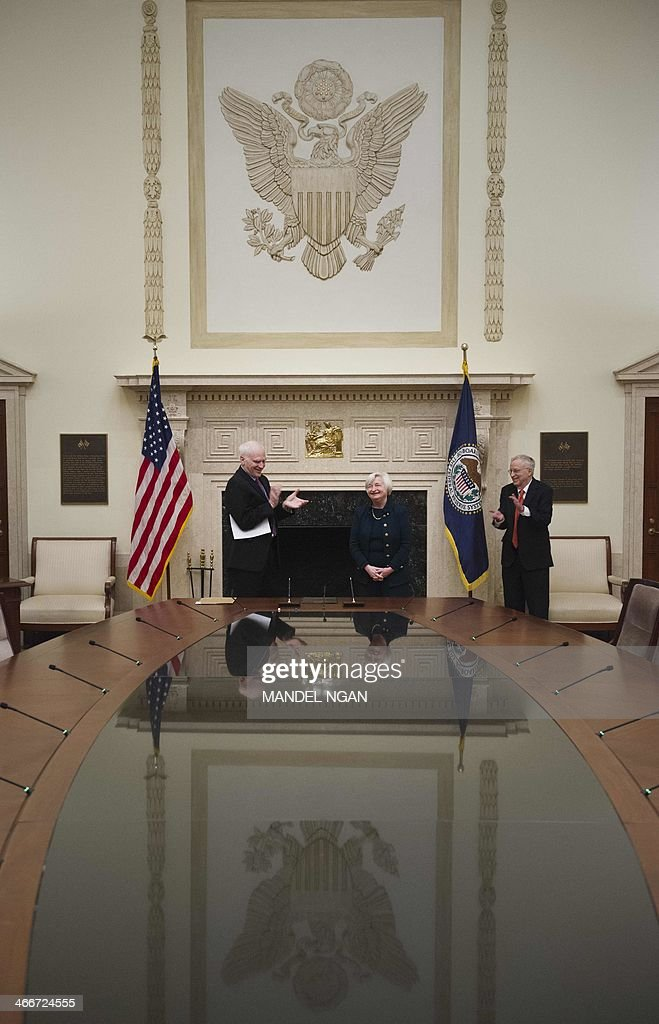 Janet Yellen (C) receives applause from Fed Governor Daniel Tarullo (L) and her husband George Akerlof after she took the oath of office as Chair of the Board of Governors of the Federal Reserve System on February 3, 2014 at the Eccles Building in Washington, DC. AFP PHOTO/Mandel NGAN