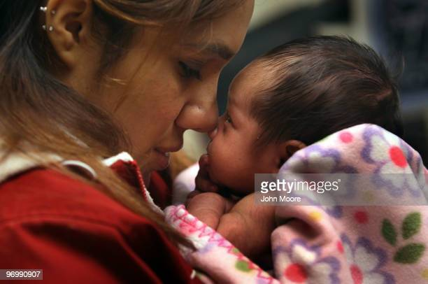 Janeth Fernandez holds her daughter Sarah during a newborn checkup on February 23 2010 in Aurora Colorado The Metro Community Provider Network which...