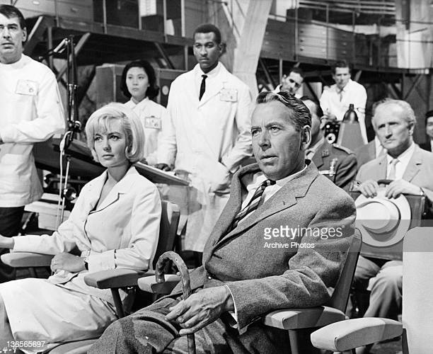 Janette Scott and Alexander Knox sitting at meeting of scientists in a scene from the film 'Crack In The World' 1965