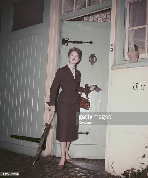 Janette Scott British actress poses leaning on an umbrella beside an open door circa 1955