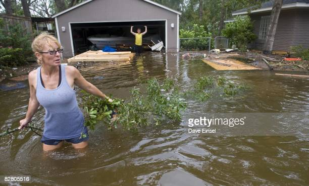 Janey Fattig clears floating debris from around her flooded home as her son Zach watches from behind September 13 2008 in League City Texas High...