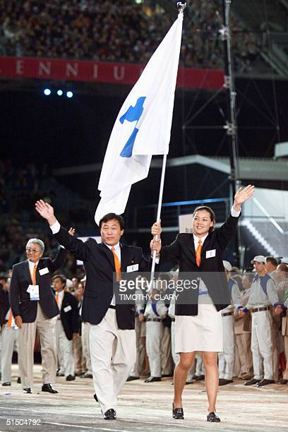 Jang Choo of North Korea and CHUNG EunSoon of South Korea carry a special flag showing the Korean peninsula as teams from the two Koreas march...