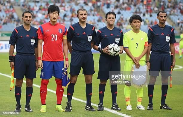 Jang Hyunsoo of South Korea and Ryota Oshima of Japan poses with match officials during the Football Mens Quarter final match between South Korea and...