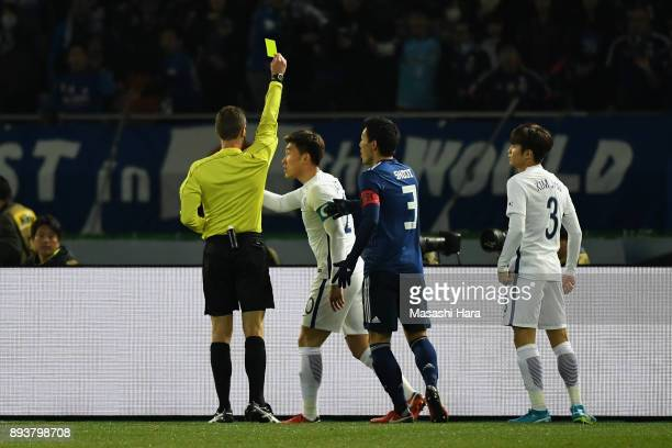 Jang Hyunsoo of South Korea is shown a yellow card by Referee Chris Beath after fouling Jyunya Ito of Japan in the penalty box during the EAFF E1...