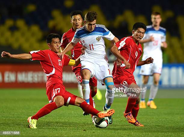 Jang Song Il and Han Kwang Song of Korea DPR battle for the ball with Alexander Lomovitskiy of Russia during the FIFA U17 World Cup Chile 2015 Group...