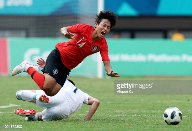 Jang Yunho of South Korea is brought down by Xanrobekov Odiljon of Uzbekistan duing the Men's Football Competition Quarter Finals match between...