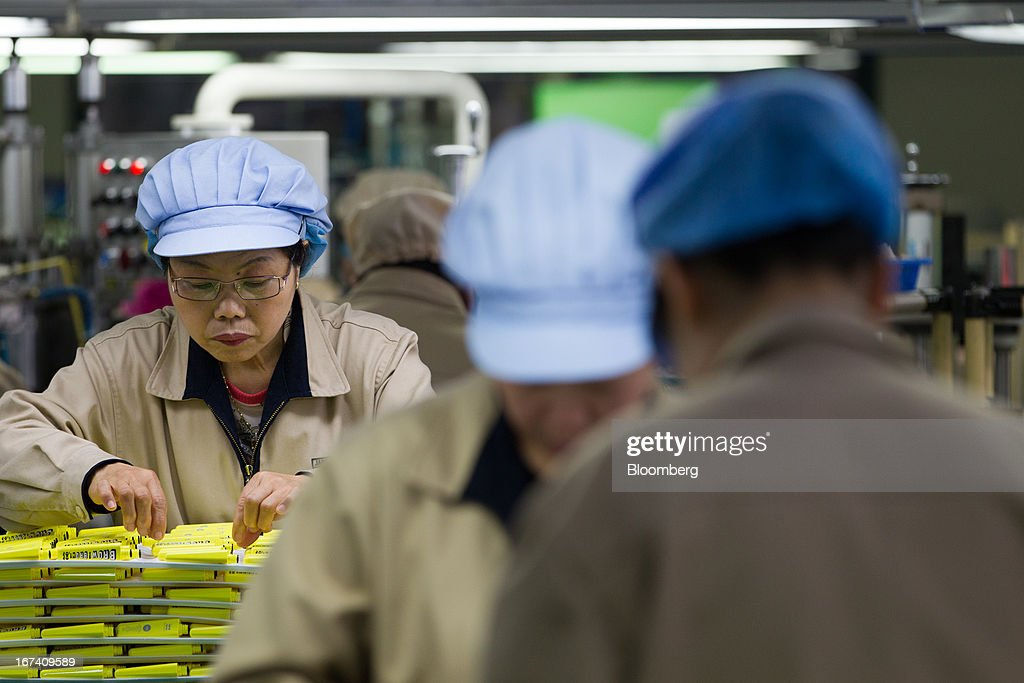 Jangup System Co. employees inspect mascara containers on the production line for manufacturing cosmetics containers at the company's factory in Yongin, South Korea, on Wednesday, April 24, 2013. South Korea's economy grew the most in two years in the first quarter as the government front-loaded spending and exporters weathered the slide in the yen that aids rivals in Japan. Photographer: SeongJoon Cho/Bloomberg via Getty Images