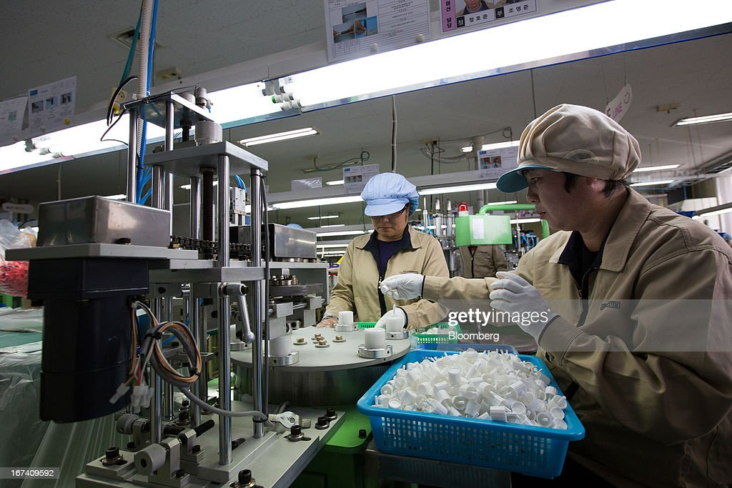 Jangup System Co. employees put lip gloss caps into an assembly machine on the production line for manufacturing cosmetics containers at the company's factory in Yongin, South Korea, on Wednesday, April 24, 2013. South Korea's economy grew the most in two years in the first quarter as the government front-loaded spending and exporters weathered the slide in the yen that aids rivals in Japan. Photographer: SeongJoon Cho/Bloomberg via Getty Images