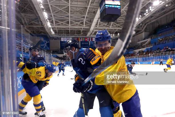 Jani Lajunen of Finland and Staffan Kronwall of Sweden collide in the third period during the Men's Ice Hockey Preliminary Round Group C game on day...