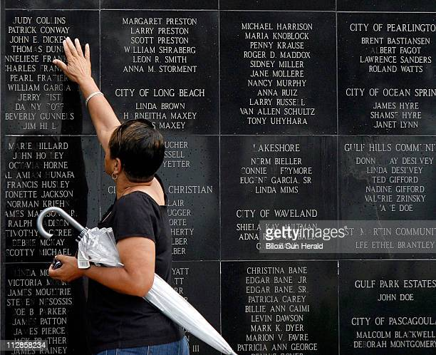 Janice Boudreaux Lee touches the name of her friend John Dickey at the Katrina Memorial at the Town Green in Biloxi Mississippi Sunday August 29 2010...