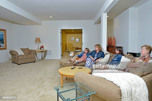 Janice Charlip relaxes in the basement family room with her daughterinlaw Aimee Norwood 10yearold Buddy and granddaughters Cassidy left and Alexia...