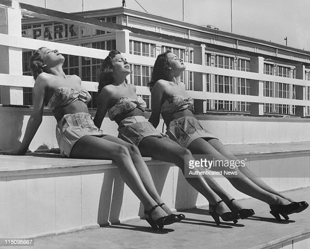 Janice Cooper, Marilyn Connor and Gloria Ellexson wearing bathing suits made from World War 2 Air Force escape maps, given to them by their...