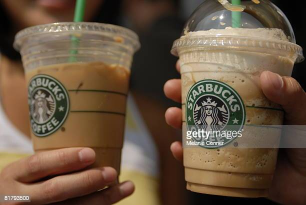 Janice Kim of Seattle and Katie Schaumann of Minnesota drink Starbucks coffees outside of the flagship Starbucks store at Pike Place July 1 2008 in...