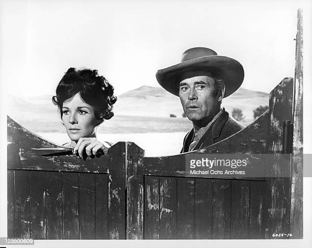 Janice Rule and Henry Fonda looking over a wooden door in a scene from the film 'Welcome To Hard Times' 1967