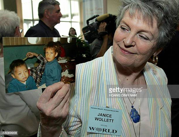 Janice Wollett a former flight attendant working on 1975 flights of the Babylift Operation shows off a picture of two Vietnam War orphans taken...