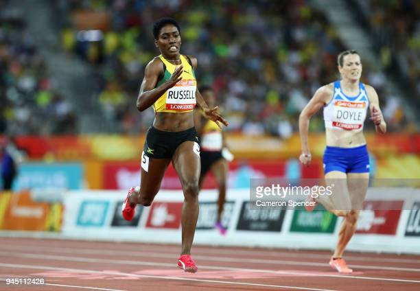 Janieve Russell of Jamaica crosses the line to win gold ahead of Eilidh Doyle of Scotland in the Women's 400 metres hurdles final during athletics on...