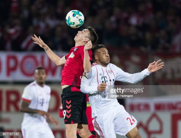 Janik Haberer of Freiburg jumps for a header with Corentin Tolisso of Muenchen during the Bundesliga match between SportClub Freiburg and FC Bayern...