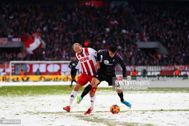 Janik Haberer of SC Freiburg battles for the ball with Konstantin Rausch of FC Koeln during the Bundesliga match between 1 FC Koeln and SportClub...