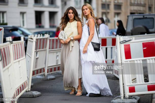 Janina Pfau is seen wearing pleated skirt and Alessa Winter is seen wearing white dress outside Nobi Talai during Berlin Fashion Week on July 04 2019...