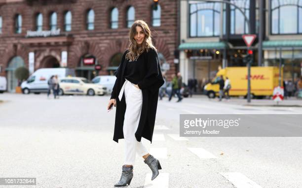 Janina Pfau wearing a Valentino cape and sweater Zara pants Moncler bag and Isabel Marant boots on October 08 2018 in Hamburg